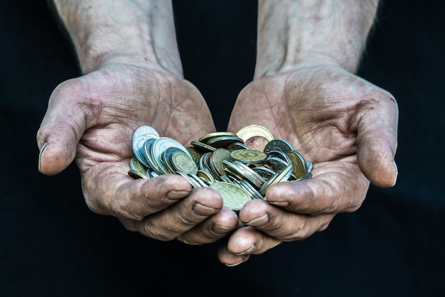 Obdachloser armer mann der schmutzigen hände mit vielen münzen aus verschiedenen ländern, die armut in der modernen kapitalismusgesellschaft veranschaulichen