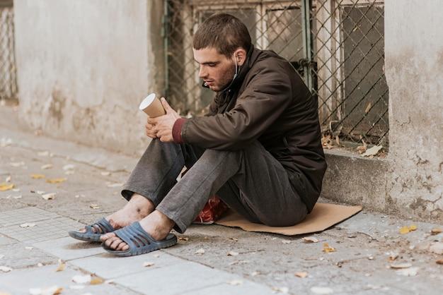 Obdachloser auf der straße mit tasse