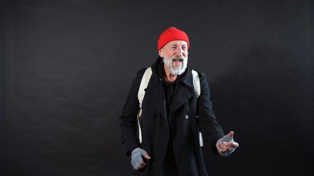 Obdachloser, ein rentner, ein alter mann mit einem grauen bart in einem mantel und einem roten hut auf einem isolierten dunklen hintergrund