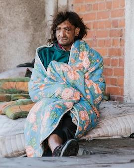 Obdachloser mann auf matratze draußen unter decke