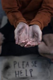 Obdachloser mann betteln mit bitte helfen zu unterschreiben