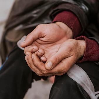 Obdachloser mann, der hände für hilfe aushält