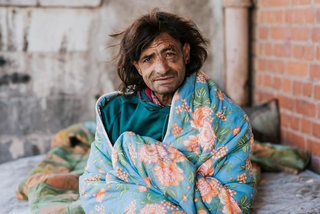 Obdachloser mann draußen unter der decke