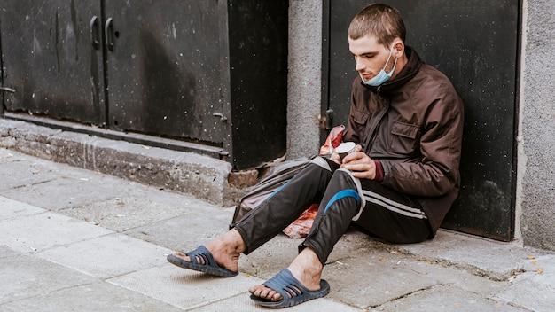 Obdachloser mit medizinischer maske und tasse