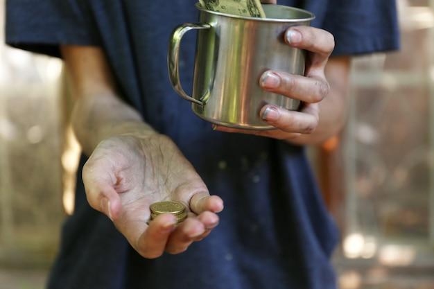 Obdachloses bettlergeld auf seinen schmutzigen händen