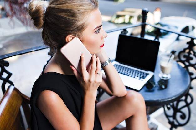 Oben ansicht ansicht nahes porträt hübsches mädchen, das am tisch auf terrasse sitzt. sie spricht am telefon.