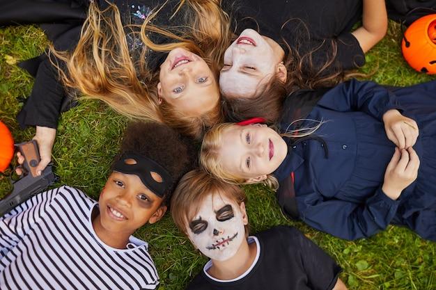Oben ansicht bei multiethnischer gruppe von kindern, die halloween-kostüme tragen, während sie auf gras liegen und