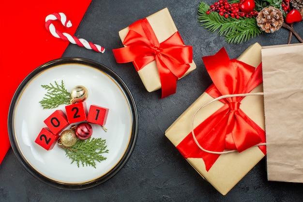 Oben ansicht der dekorationszubehörnummern auf einem teller und schönen geschenken tannenzweigen nadelbaumkegel auf einem dunklen tisch
