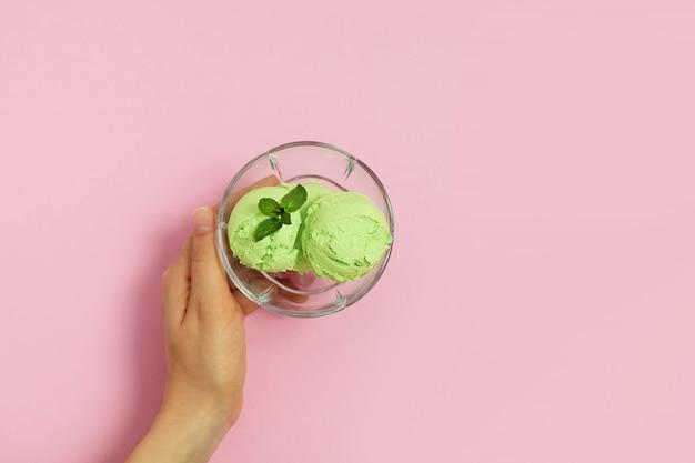 Oben ansicht der frauenhand, die glasschale mit gesundem veganem avocado-eis hält