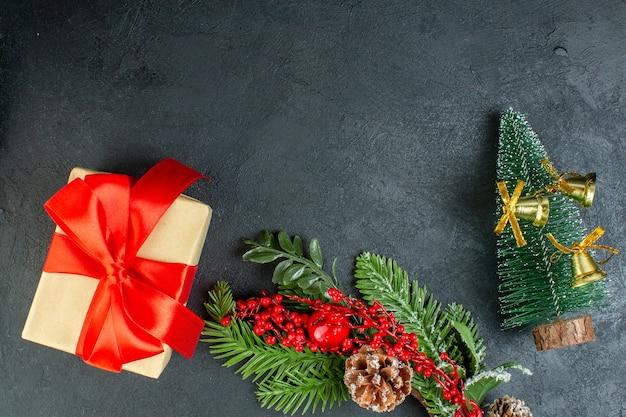 Oben ansicht der geschenkbox mit bogenförmigem roten band-tannenzweig-nadelbaumkegel-weihnachtsbaum auf schwarzem hintergrund