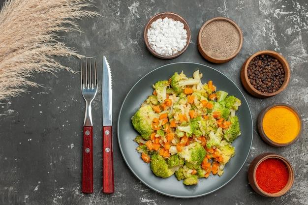 Oben ansicht der gesunden mahlzeit mit brokkoli und karotten auf einem schwarzen teller und gewürzen auf grauem tisch
