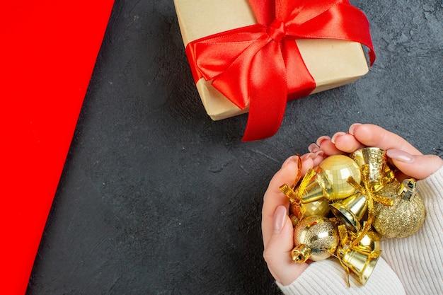 Oben ansicht der hand, die bunte dekorationszubehör und schönes geschenk auf rotem handtuch auf dunklem hintergrund hält