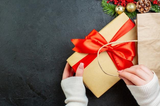 Oben ansicht der hand, die eine schöne geschenkbox auf dunklem hintergrund hält