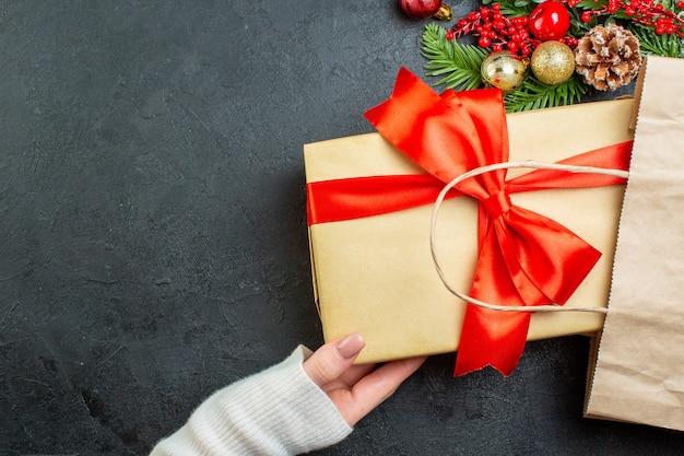 Oben ansicht der hand, die eine schöne geschenkbox aus einer tasche auf dunklem hintergrund herausnimmt