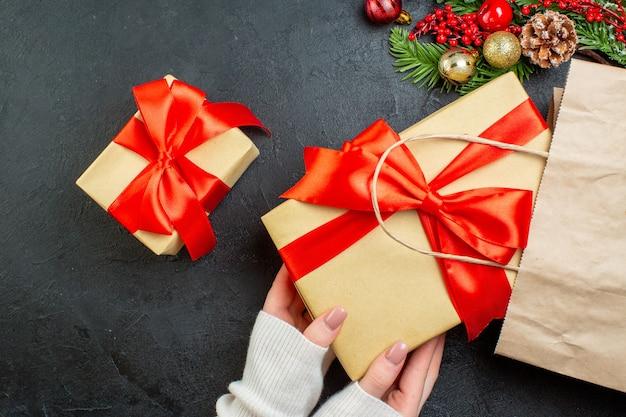 Oben ansicht der hand, die eine schöne geschenkbox aus einer tasche auf schwarzem hintergrund herausnimmt