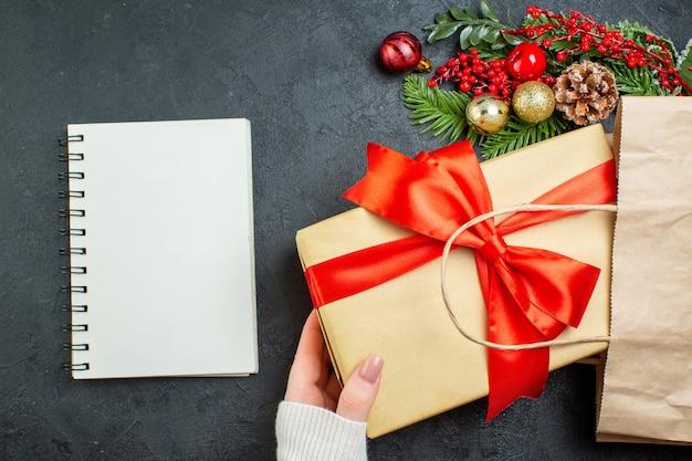 Oben ansicht der hand, die eine schöne geschenkbox aus einer tasche neben notizbuch auf dunklem hintergrund herausnimmt