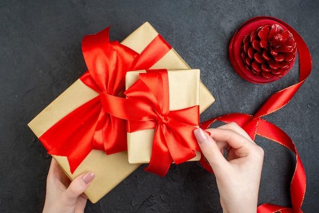 Oben ansicht der hand, die schönes geschenk und nadelbaumkegel auf dunklem hintergrund hält