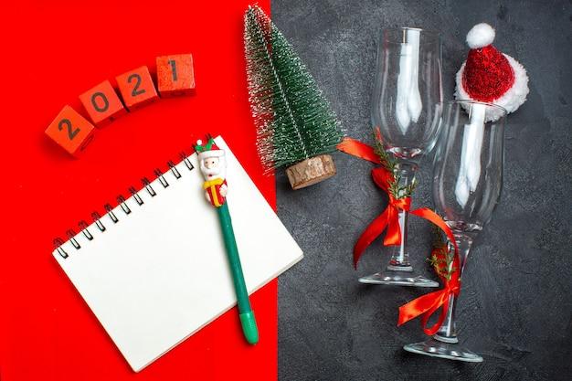 Oben ansicht der hand, die spiralnotizbuch und weihnachtsbaumglasbechernummern auf dunklem und rotem hintergrund hält