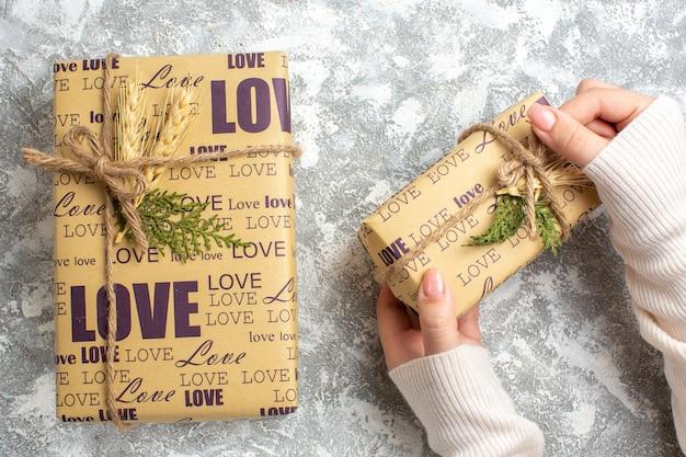 Oben ansicht der hand, die verpacktes geschenk für weihnachten auf der eisoberfläche hält