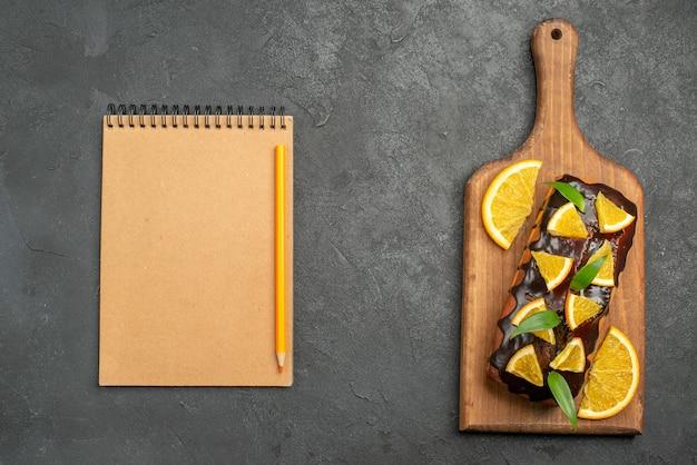 Oben ansicht der köstlichen kuchen, die mit orange und schokolade auf schneidebrett neben notizbuch verziert werden
