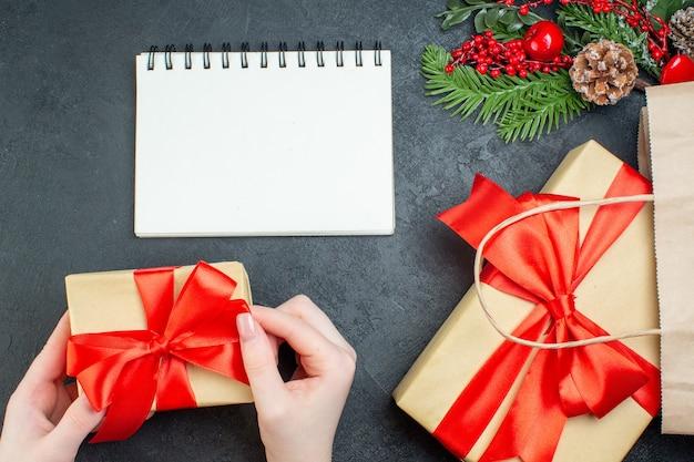 Oben ansicht der weihnachtsstimmung mit hand, die eines der schönen geschenke und tannenzweige nadelbaumkegel neben notizbuch auf dunklem hintergrund hält