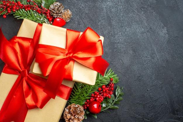 Oben ansicht der weihnachtsstimmung mit schönen geschenken mit bogenförmigem band und tannenzweigdekorationszubehör auf der rechten seite auf einem dunklen hintergrund