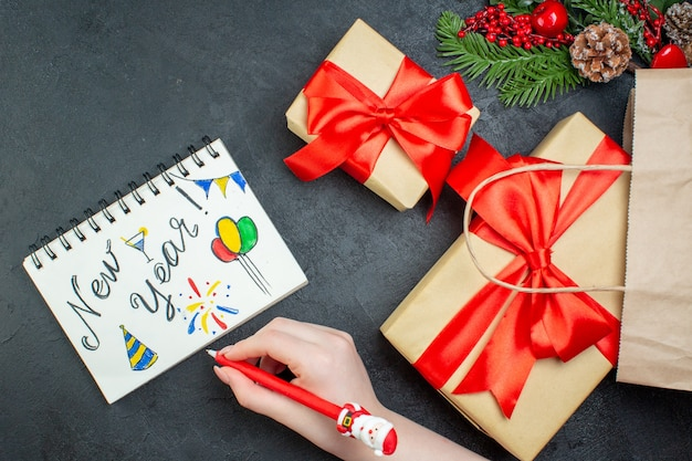 Oben ansicht der weihnachtsstimmung mit schönen geschenken und tannenzweigen nadelbaumkegel neben notizbuch mit neujahrszeichnungen auf dunklem hintergrund