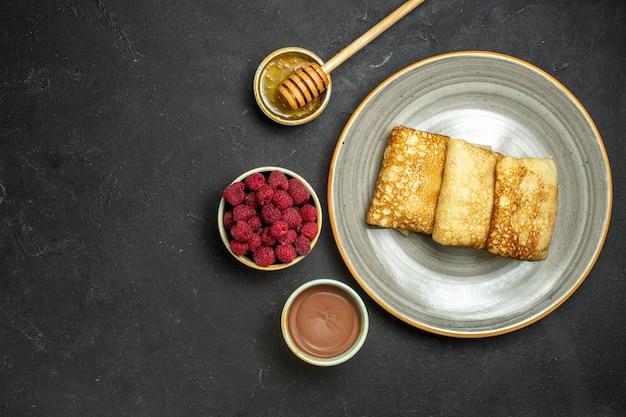 Oben ansicht des abendessenhintergrundes mit köstlichem pfannkuchenhonig und schokoladenhimbeere auf schwarzem hintergrund
