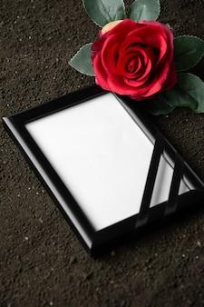 Oben ansicht des bilderrahmens mit roter blume auf dunklem boden sensenmann-todesbestattungsporträt