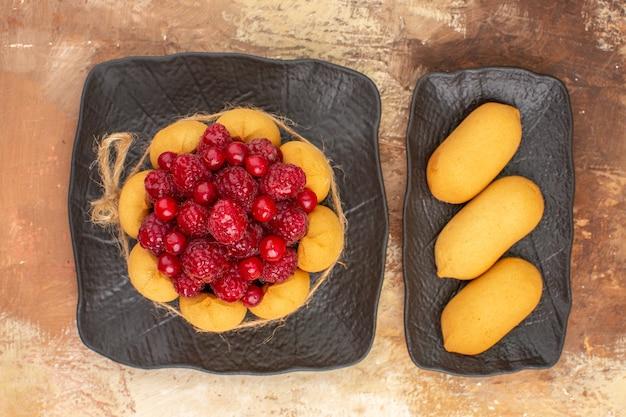 Oben ansicht des gedeckten tisches mit einem geschenkkuchen für gäste auf gemischtem farbtisch