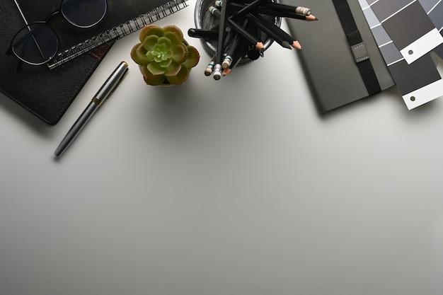Oben ansicht des grafikdesignerarbeitsplatzes mit farbmustern, bleistifthalter, notizbuch und kopienraum auf weißem tisch.