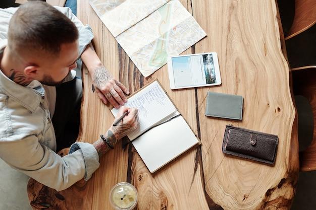 Oben ansicht des jungen mannes mit tätowierungen, die am holztisch mit brieftasche, tablette, karte sitzen und notizen über reise im planer machen