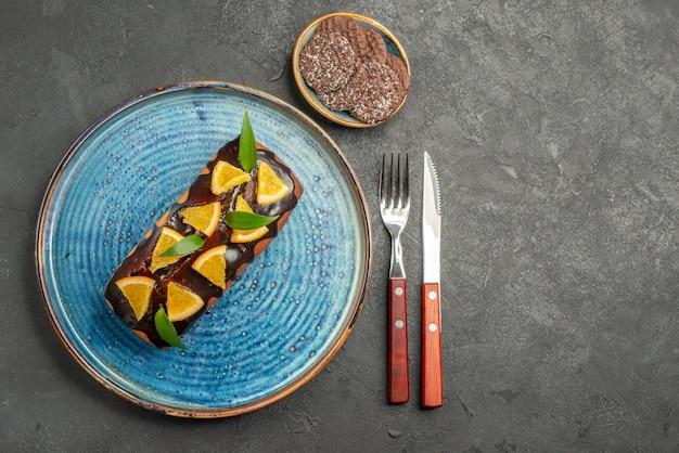 Oben ansicht des köstlichen kuchens, der orange mit schokolade und keksen auf schwarzem tisch verziert wird