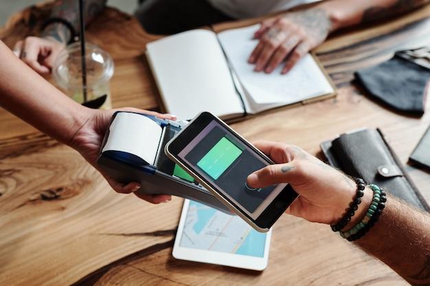 Oben ansicht des männlichen gastes mit armbändern, die smartphone zum terminal setzen, während kontaktloses bezahlen im café verwendet wird
