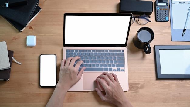 Oben ansicht des mannes, der mit laptop auf hölzernem schreibtisch arbeitet.