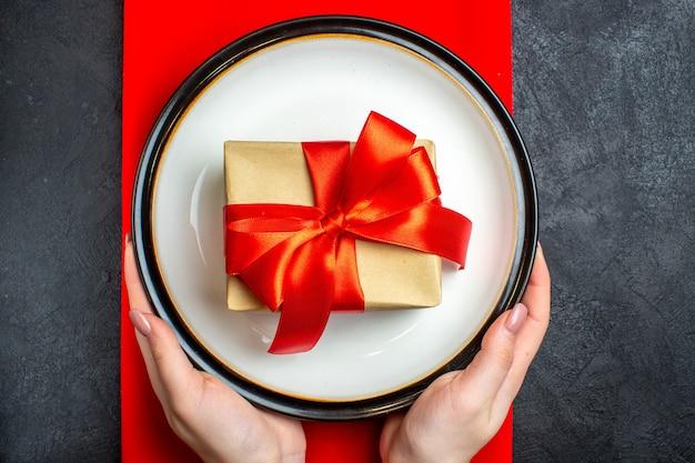 Oben ansicht des nationalen weihnachtsmahlzeithintergrundes mit hand, die leere teller mit bogenförmigem rotem band auf einer roten serviette auf schwarzem tisch hält