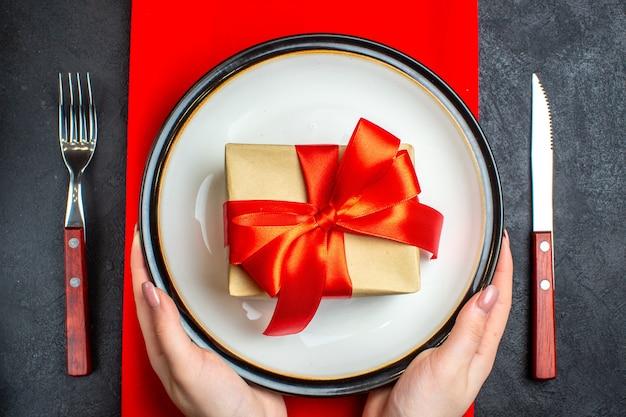 Oben ansicht des nationalen weihnachtsmahlzeithintergrundes mit hand, die leere teller mit bogenförmigem rotem band auf einer roten serviette und besteck auf schwarzem tisch hält