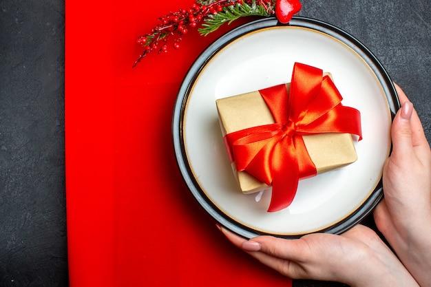 Oben ansicht des nationalen weihnachtsmahlzeithintergrundes mit hand, die leere teller mit bogenförmigem rotem band und tannenzweigen auf einer roten serviette auf schwarzem tisch hält