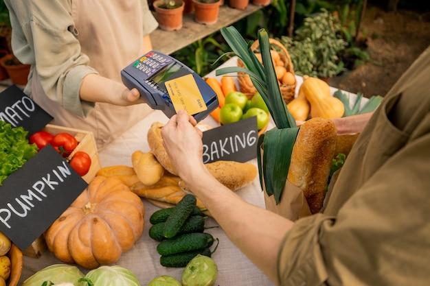 Oben ansicht des nicht erkennbaren kunden, der kreditkarte zum terminal setzt, während für bio-lebensmittel auf dem bauernmarkt bezahlt wird