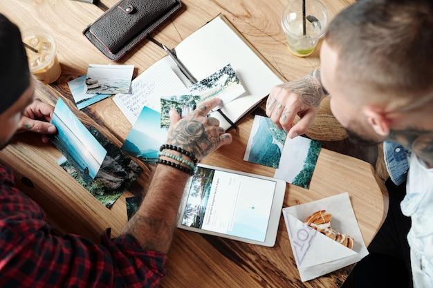 Oben ansicht des reisenden, der am tisch mit szenischen fotos sitzt und einem freund ratschläge über die reiseroute gibt