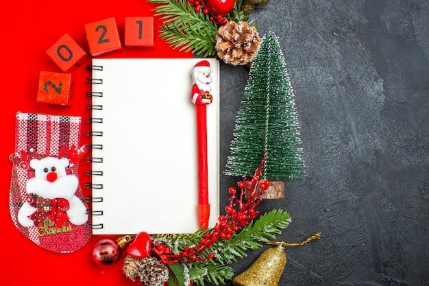 Oben ansicht des spiralförmigen notizbuchdekorationszubehörs tannenzweige-weihnachtssockenzahlen auf einer roten serviette und weihnachtsbaum auf dunklem hintergrund