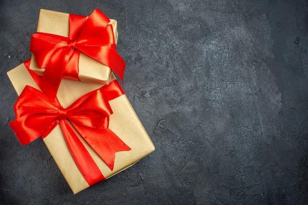 Oben ansicht des weihnachtshintergrundes mit schönen geschenken mit bogenförmigem band auf der rechten seite auf einem dunklen hintergrund