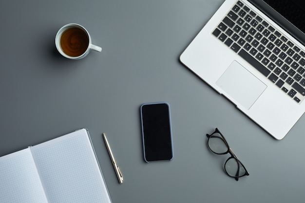 Oben ansicht flache lage von laptop und geschäftszubehör auf grauem arbeitsplatzhintergrund,