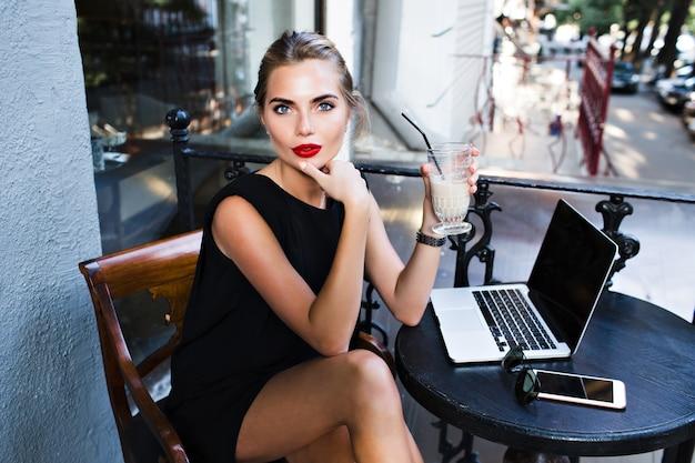 Oben ansicht hübsche frau im schwarzen kurzen kleid, das am tisch auf terrasse in der cafeteria sitzt. sie schaut zur kamera.