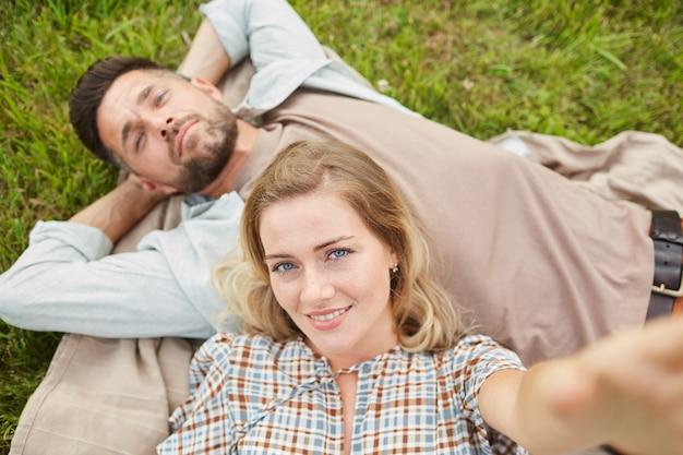 Oben ansicht-porträt des sorglosen erwachsenen paares, das selfie nimmt, während auf grünem gras im park liegend