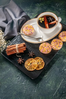 Oben ansicht tasse tee mit süßen keksen in teller und tablett auf dunkler oberfläche zeremonie glas süße frühstückstorte dessert farbe zucker