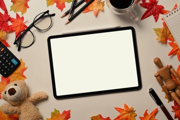 Oben ansicht verspotten digitale tablette auf weißem tisch mit herbstahornblättern.