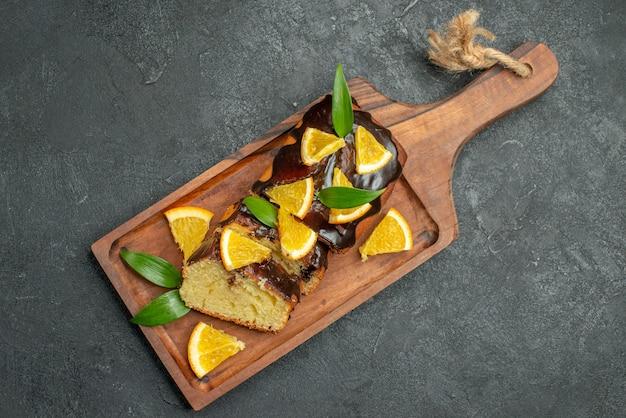 Oben ansicht von frisch gebackenen weichen kuchenscheiben auf hölzernem schneidebrett auf dunklem tisch