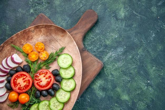 Oben ansicht von frisch gehacktem gemüse in einem braunen teller auf hölzernem schneidebrett auf der rechten seite auf gemischten farbtabellen
