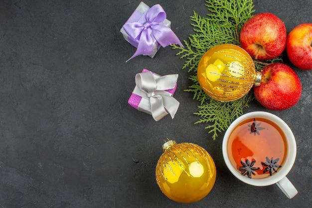 Oben ansicht von geschenken und organischen frischen äpfeln dekorationszubehör und eine tasse schwarzen tee auf dunklem hintergrund